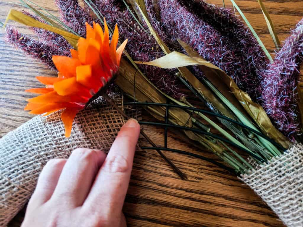 Photo of an artificial fall leaf being attached to a wreath wire frame that is wrapped in burlap ribbon with artificial lavender leaves.