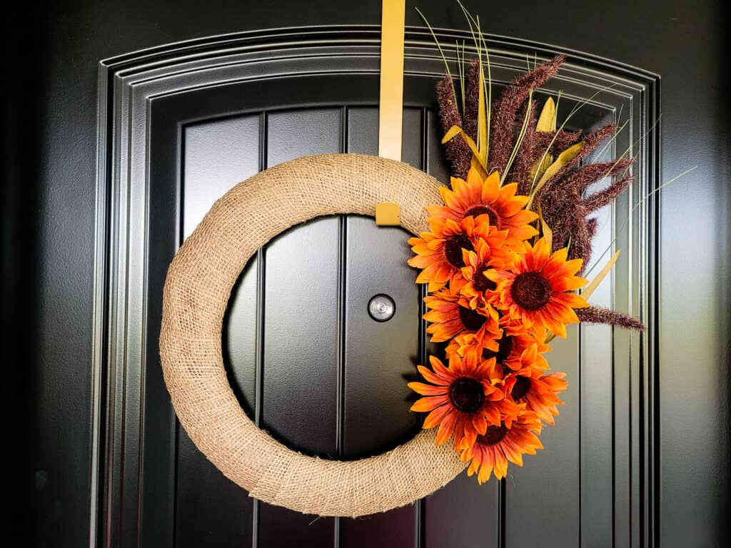 Photo of a wreath made of burlap ribbon and artificial fall leaves and lavender stems hanging on a front door.