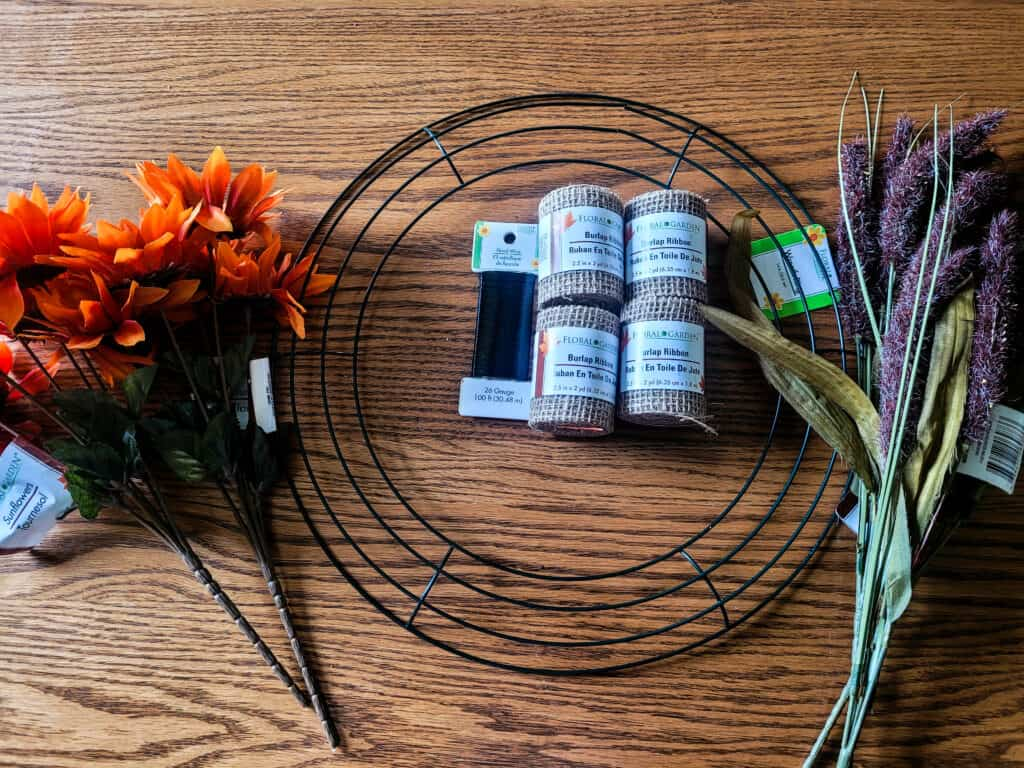 Photo of all the supplies needed to make a wreath of burlap ribbon and artificial fall leaves and lavender stems.