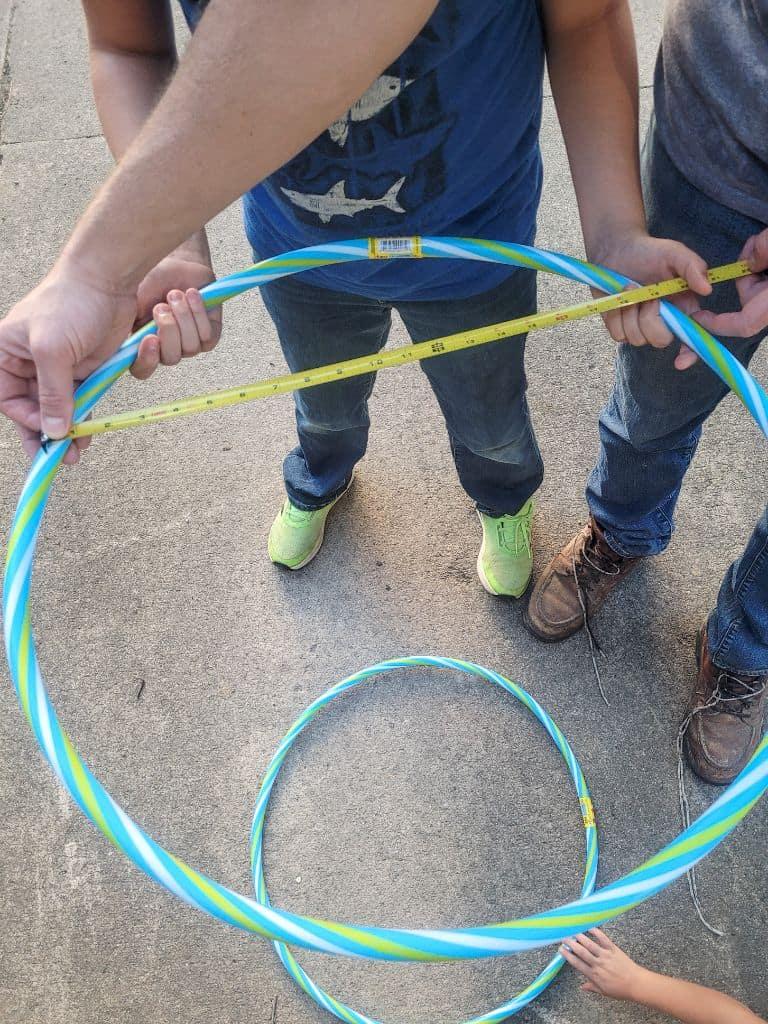 photo of people measuring a plastic hoop