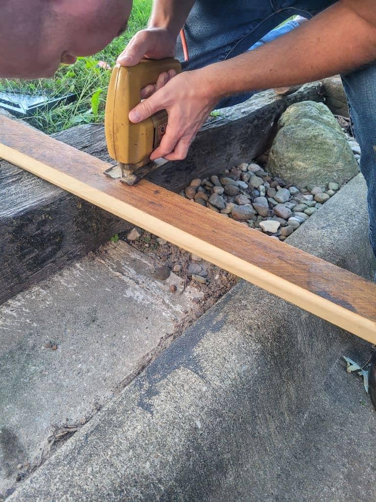 photo of a man cutting a board with a jigsaw