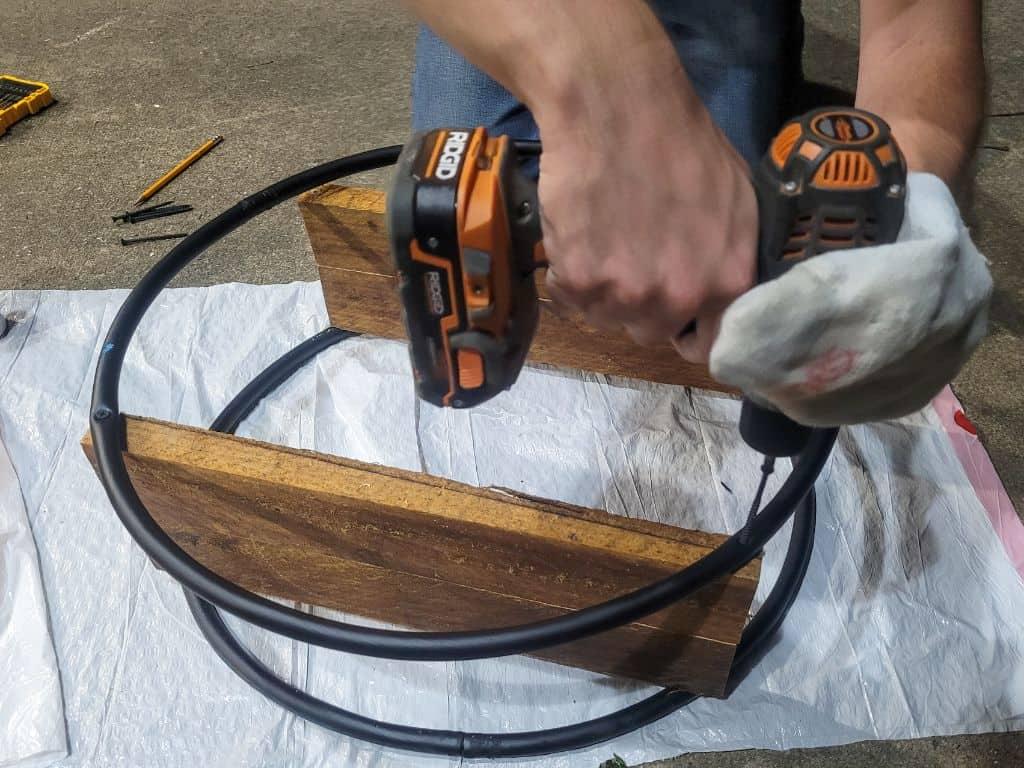 photo of a man drilling screws into a hoop book shelf
